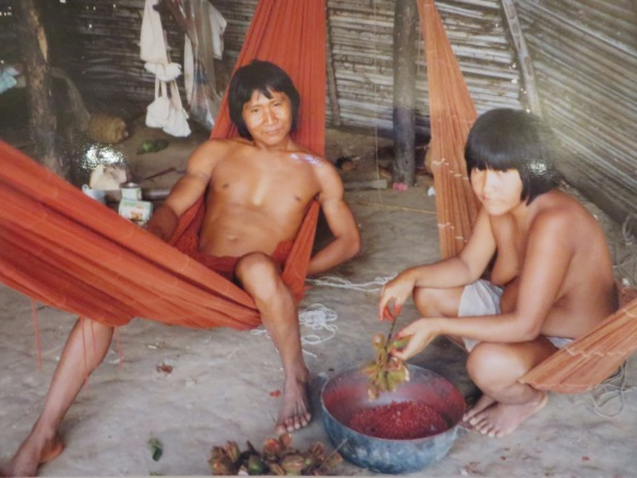 A couple in their hut in Amazonia. The woman is plucking berries to be used as dye for new cloth (seen in background)